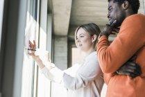 Mujer de negocios casual y hombre de negocios discutiendo el papel en la ventana - foto de stock