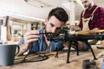 Человек, работающий на дроне в мастерской — стоковое фото