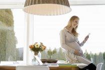 Улыбающаяся беременная женщина сидит на столе и смотрит на мобильный телефон — стоковое фото