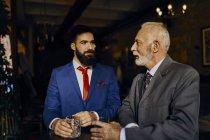 Due uomini eleganti in un bar con bicchieri — Foto stock