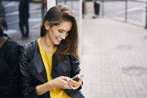 Mulher feliz que olha o telefone de pilha — Fotografia de Stock
