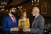 Due uomini e donne eleganti che socializzano in un bar — Foto stock