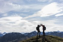 Austria, Tyrol, young couple standing in mountainscape and cheering — Stock Photo