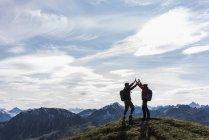 Австрия, Тироль, молодая пара, стоящая в горах и ликующая — стоковое фото