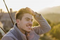 Портрет улыбающегося молодого человека с рукой в волосах на закате — стоковое фото