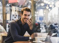 Giovane uomo d'affari sorridente in un caffè alla stazione ferroviaria con cellulare e laptop — Foto stock