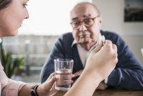 Mujer sosteniendo píldora y vaso de agua para hombre mayor - foto de stock