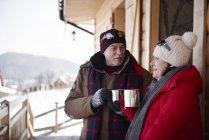 Зріла пара з гарячими напоями Говорячи на відкритому повітрі в гірській Хатині взимку — стокове фото