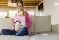 Портрет улыбающейся беременной женщины, сидящей на диване и держащей наушники у живота — стоковое фото