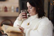 Зрелая женщина с горячим напитком читает книгу — стоковое фото