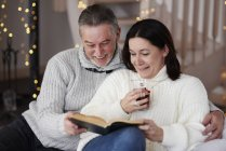 Happy mature couple reading a book in living room — Stock Photo