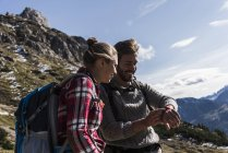 Austria, Tyrol, smiling young couple looking at watch in mountainscape — Stock Photo