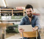 Smiling man sitting on chair in workshop — Stock Photo