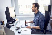 Lächelnder Grafikdesigner arbeitet am Computer am Schreibtisch im Büro — Stockfoto