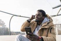 Улыбающийся молодой африканский американец со смартфоном и наушниками на улице — стоковое фото