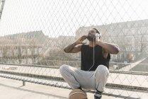 Joueur afro-américain de basket-ball sur le terrain accroupi à la clôture et écouter de la musique — Photo de stock