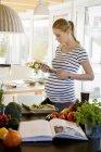 Беременная женщина на кухне дома с помощью планшета — стоковое фото