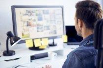 Editeur photo travaillant sur ordinateur au bureau — Photo de stock
