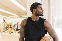 African american Man with tattoos holding basketball ball and looking away — Stock Photo