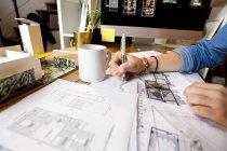 Giovane donna che lavora nello studio di architettura, disegnando cianografie — Foto stock