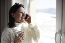 Улыбающаяся женщина на телефоне у окна — стоковое фото