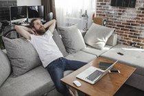 Uomo sorridente che si rilassa sul divano di casa — Foto stock