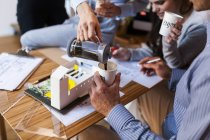 Team di architetti che lavorano a un progetto, bevono caffè — Foto stock