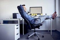Людина, сидячи на столі в офісі і розслабляючий — стокове фото
