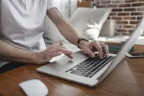 Las manos del hombre en el teclado y el panel táctil de la computadora portátil, vista parcial - foto de stock