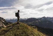 Österreich, Tirol, junger Mann steht in der Berglandschaft und blickt auf die Aussicht — Stockfoto