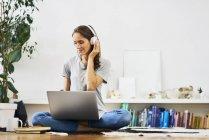 Mujer joven y relajada en casa sentada en el suelo, usando un ordenador portátil y escuchando música - foto de stock