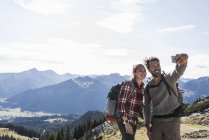Austria, Tyrol, smiling young couple taking a selfie in mountainscape — Stock Photo