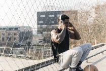 Улыбающийся африканский американский баскетболист на корте, приседающий к забору и слушающий музыку — стоковое фото