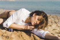 Приваблива молода жінка, що лежить в піску на пляжі — стокове фото