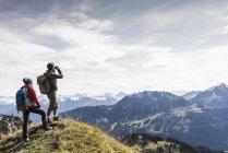 Austria, Tirol, pareja joven de pie en el paisaje de montaña y mirando a la vista - foto de stock