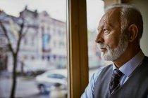 Homem sênior elegante olhando pela janela — Fotografia de Stock