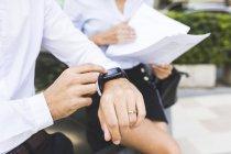 Бизнесмен с умными часами и бизнесвумен с документами в городе — стоковое фото