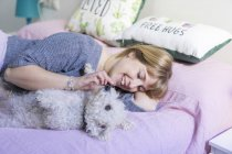 Happy woman lying on bed with her dog — Stock Photo