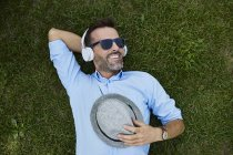 Портрет смеющегося человека, расслабляющегося на лугу, слушающего музыку в наушниках и держащего шляпу — стоковое фото