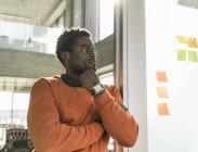 Случайный бизнесмен в офисе у стены с клейкими нотами — стоковое фото