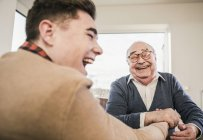 Happy senior man and young man arm wrestling — Stock Photo