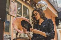 Ritratto di giovane donna sorridente in piedi davanti al negozio di antiquariato guardando il disco di grammofono — Foto stock