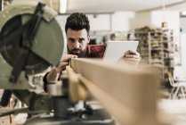 Man in workshop with piece of wood and tablet — Stock Photo