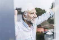 Portrait of happy mature man looking out of windowpane — Stock Photo