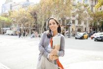Ritratto di donna sorridente che tiene il quaderno in città — Foto stock
