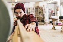 Homme examinant le bois en atelier — Photo de stock