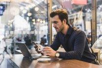 Молодой бизнесмен в кафе на вокзале с сотовым телефоном и ноутбуком — стоковое фото