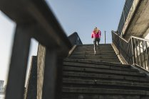 Young woman running up stairs — Stock Photo