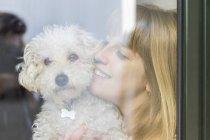 Happy woman behind windowpane cuddling her dog — Stock Photo