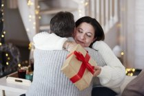 Happy mature couple with gift box hugging in living room — Stock Photo
